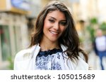Portrait of a beautiful young woman smiling in urban background - stock photo