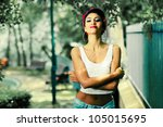 Portrait of a pin-up girl in a garden wearing jeans and t-shirt - stock photo