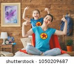 mother and her child playing... | Shutterstock . vector #1050209687