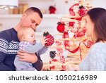 happy young family decorate... | Shutterstock . vector #1050216989