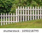 Small photo of High and low sections of weathered white picket fence across hilly lawn