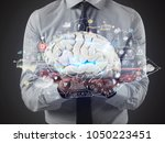 man holds a brain with business ... | Shutterstock . vector #1050223451