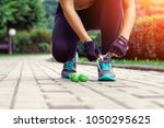 sports concepts   woman tying... | Shutterstock . vector #1050295625