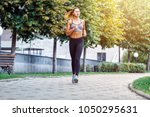 a beautiful sporty woman runing ... | Shutterstock . vector #1050295631