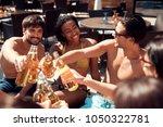 joyful friends cheering with... | Shutterstock . vector #1050322781