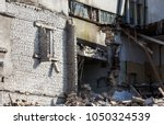 Small photo of An abandoned house collapses in a poor neighborhood. The house is destroyed. Cracks in wall of house. Destruction of old houses, earthquakes, economic crisis, abandoned houses. Broken unfit house