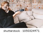 blonde woman sitting on couch...   Shutterstock . vector #1050324971