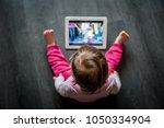 toddler sitting on the floor... | Shutterstock . vector #1050334904
