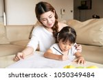 asian happy mother teaching her ... | Shutterstock . vector #1050349484