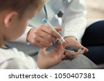 doctor using lancet pen and... | Shutterstock . vector #1050407381