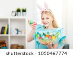 teenage girl holding easter eggs | Shutterstock . vector #1050467774