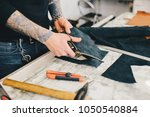 man working with leather using... | Shutterstock . vector #1050540884