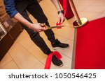 a man is cutting a red ribbon... | Shutterstock . vector #1050546425