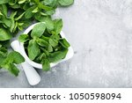 fresh mint leafs in mortar on... | Shutterstock . vector #1050598094