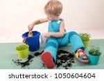 happy blond boy helps plant... | Shutterstock . vector #1050604604