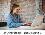 young woman working on laptop... | Shutterstock . vector #1050638459