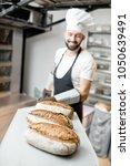baker carrying shovel with... | Shutterstock . vector #1050639491