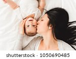 mother with a baby on bed at... | Shutterstock . vector #1050690485