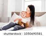 mother with a baby on bed at... | Shutterstock . vector #1050690581