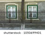 Small photo of Couple of green windows in Romania, adorned iron rusted fence
