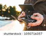 man holding in his hands remote ... | Shutterstock . vector #1050716357