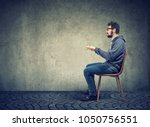 side view of casual man sitting ... | Shutterstock . vector #1050756551