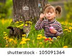 Stock photo funny lovely little girl and a cat blowing soap bubbles 105091364