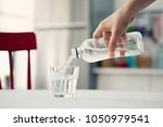 woman  pouring water from... | Shutterstock . vector #1050979541