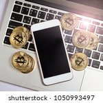 bitcoin and iphone on laptop... | Shutterstock . vector #1050993497