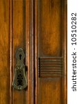 An antique lock inset into an aged wood panel door - stock photo