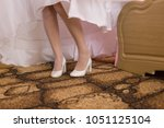 the bride is trying on shoes ... | Shutterstock . vector #1051125104