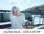 Small photo of Cannot stand it anymore. Annoyed senior lady in casual attire touching her head while sitting at a riverwalk and suffering from a terrible headache outdoors.