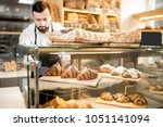 seller putting delicious... | Shutterstock . vector #1051141094