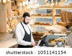 handsome bread seller working... | Shutterstock . vector #1051141154