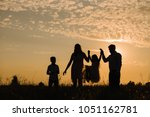 family on sunset background.... | Shutterstock . vector #1051162781