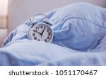 alarm clock on soft blue... | Shutterstock . vector #1051170467