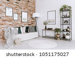 posters on red brick wall above ... | Shutterstock . vector #1051175027
