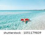 woman on lilo in the sea water. ... | Shutterstock . vector #1051179839