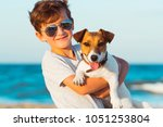 Stock photo happy year old boy hugging his dog breed jack russell at the seashore against a blue sky close up 1051253804