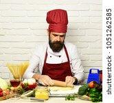 man with beard rolls out dough...   Shutterstock . vector #1051262585