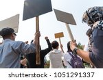 Small photo of Men and women share a protest sign hold a megaphone. Mob concept, The youth crowd gathered to protest.