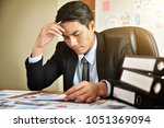 stressed young asian... | Shutterstock . vector #1051369094