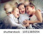 three little girls lying in bed ... | Shutterstock . vector #1051385054