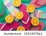 Summer fun time and flip flops. Slippers and orange fruit on blue wooden background. Mock up and picturesque. Top view. Sandals