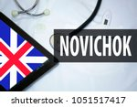 "Small photo of Medical bathrobe, tablet with English flag and inscription with Russian in Latin transcription - ""Novichok"". News concept"