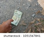a hand reaching out to pick...   Shutterstock . vector #1051567841