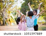 asian children raise hands and... | Shutterstock . vector #1051597889