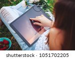 young woman using a tablet pc... | Shutterstock . vector #1051702205