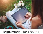 young woman using a tablet pc... | Shutterstock . vector #1051702211