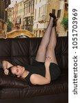 Small photo of Cute fat girl posing on a leather sofa. Pretty woman in an agitated black dress and pantyhose in a net. Beautiful and long female feet and high-heeled shoes. Juicy girl